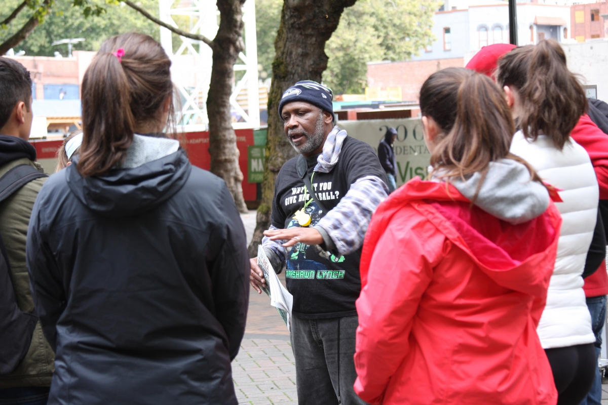 Longtime Real Change vendor Addis Michael Jr. speaks to a group of students in Occidental Park for the Homeless Speakers Bureau.