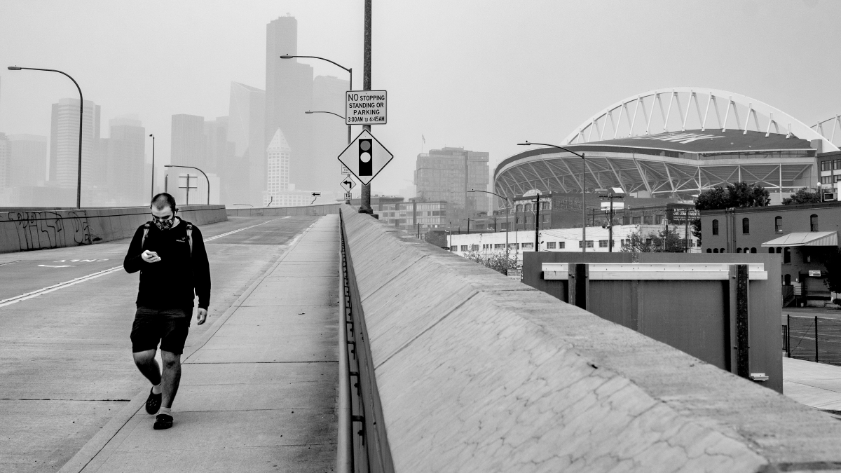 A resident walks in sodo, just south of downtown, Sept. 13 through the multi-fire smog hanging over Seattle. Photo by Mark White
