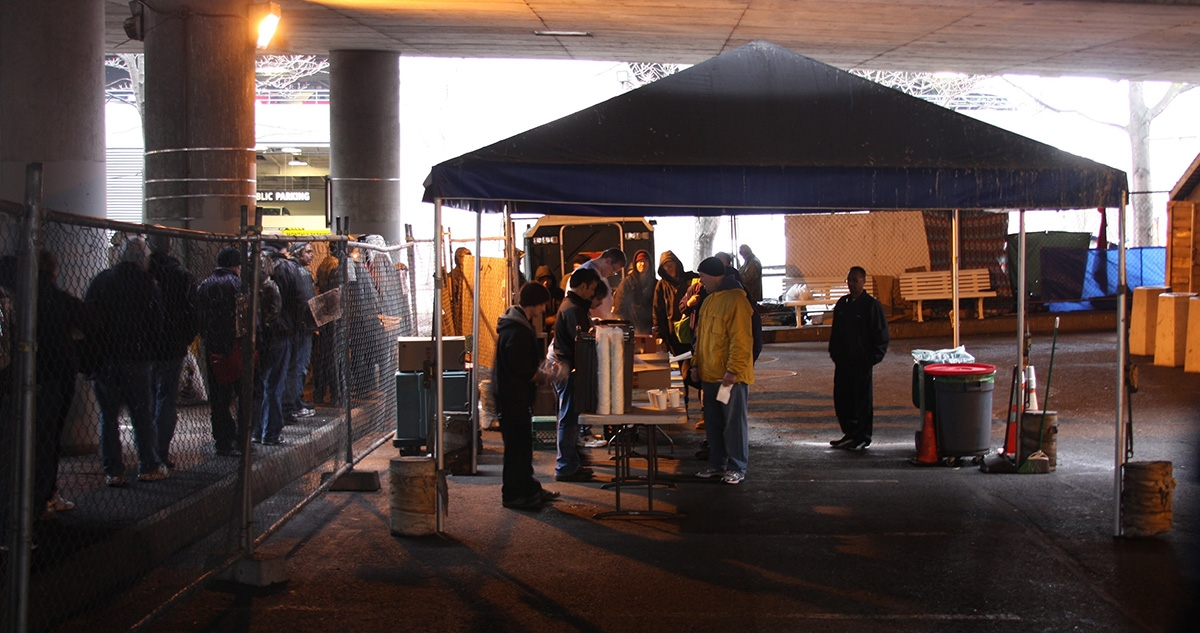Above, under Interstate 5 in Seattle, people eat a daily meal served by Operation Sack Lunch. New federal homelessness leader Robert Marbut, below right, is known for his proposals to crack down on public food distribution.