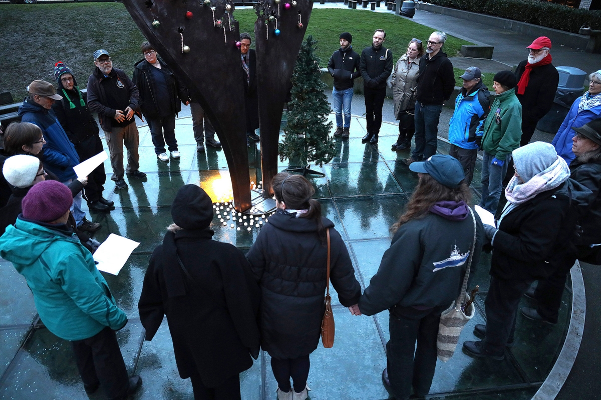 People  gather around the Tree of Life on winter solstice to memorialize those who died on the streets of Seattle during 2019.