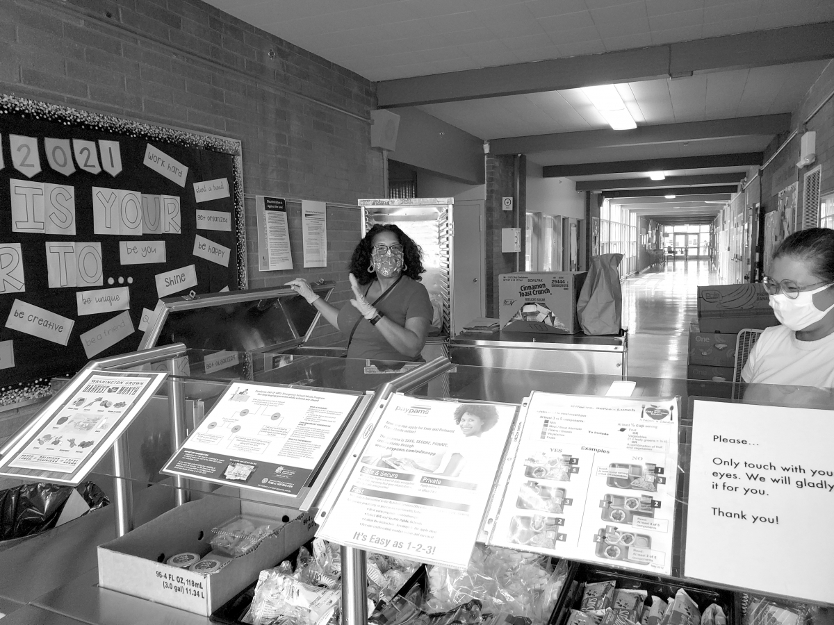 Zelda Norman and Maryanne Decena wait for students to pick up meals at Rainier View Elementary School. The program is open to families of all income levels because of a federal government waiver that expires at the end of the year. Photo by Ashley Archiba