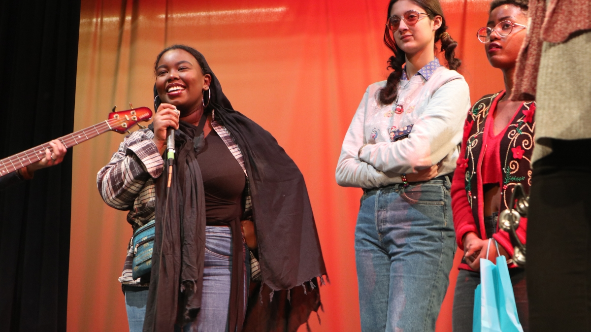 Amina, on the microphone, is a poet who found community with Totem Star. The lockdown has been difficult for this self-described social butterfly, but regular meetings with her friends and mentors at the organization help make a bad situation better.