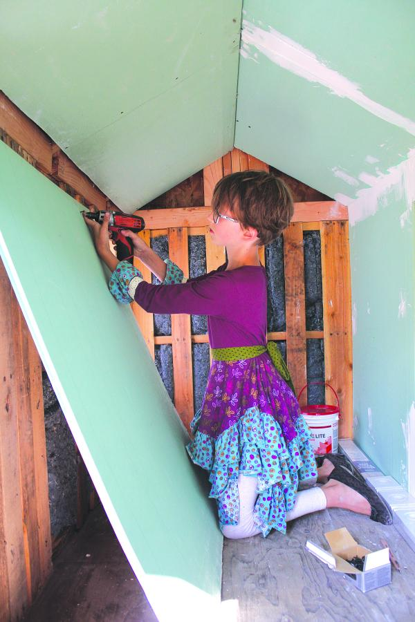 Nine-year-old Hailey Fort hangs drywall in a home she's building for a homeless friend in Bremerton.