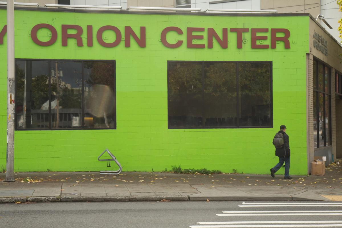Image of Orion Center for homeless youth downtown. A man walks away from the building in the right side of the frame.