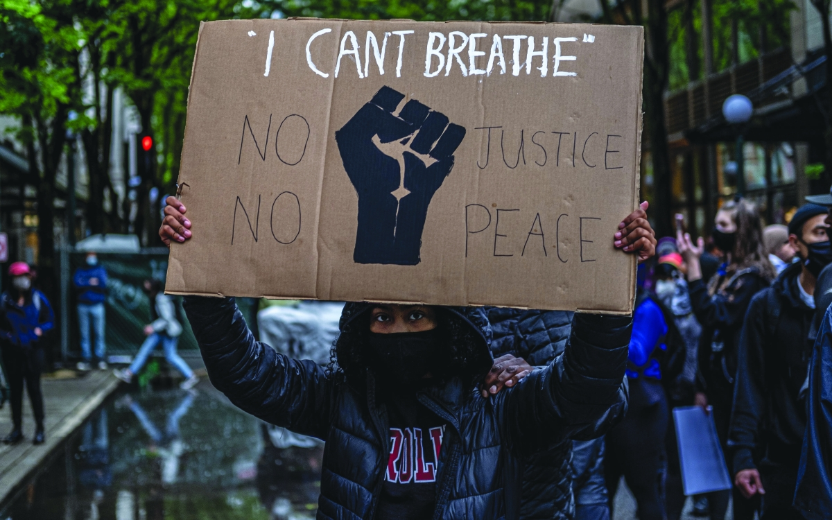 A Seattle protester holds a sign quoting the last words of both George Floyd and Eric Garner — Black men who were killed by white police officers, Floyd in Minneapolis and Garner in New York.
