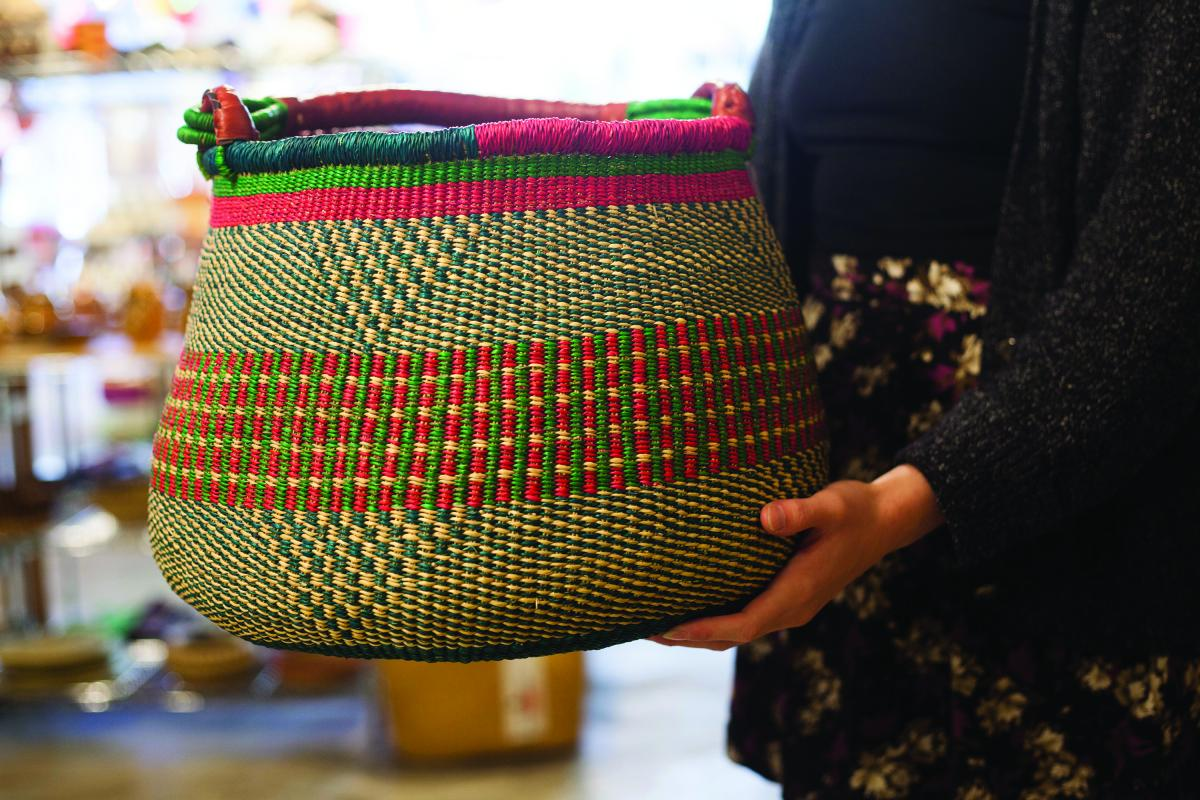 Woman holding a Gambibgo pot basket made in northern Ghana out of elephant grass.