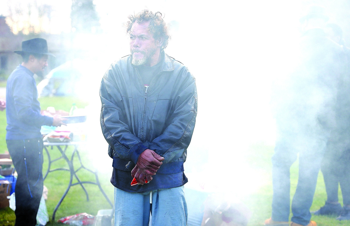 Fuáriva stands in the smoke of a barbeque  while waiting for some food at People's Park in Tacoma. Fuáriva and others who live in the park are safe staying there for the time being.