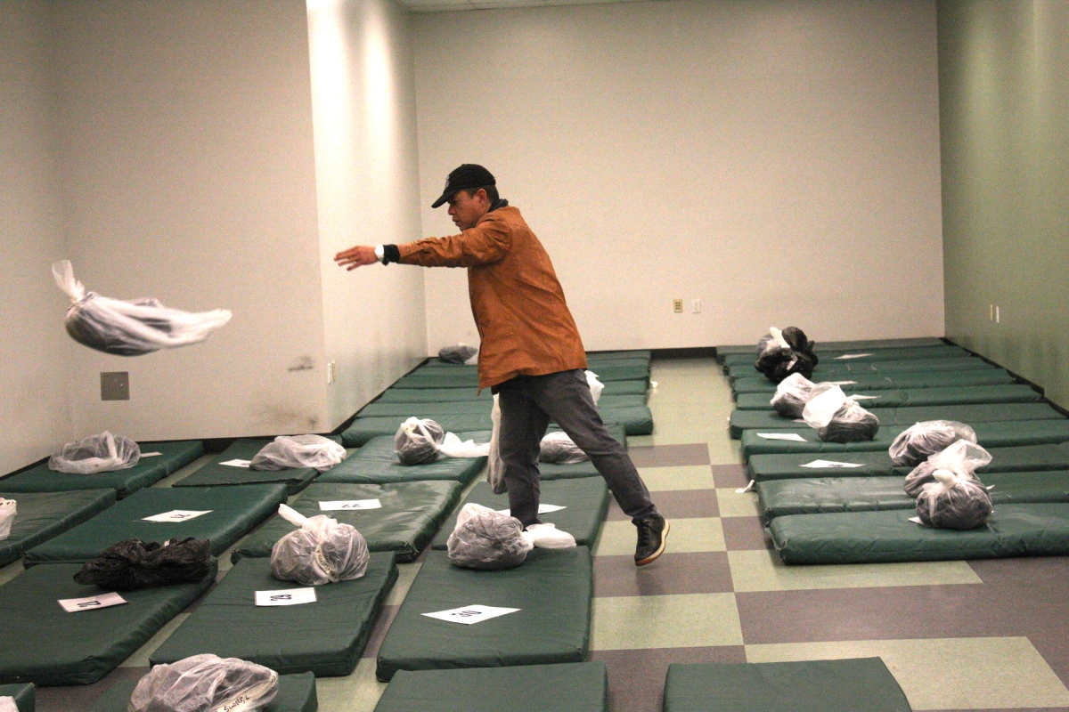 A worker, above, places blankets on mats at the Seattle City Hall shelter. The Navigation Team refers people to shelters only when they have beds available. However, more than 90 percent of shelter beds are filled nightly.