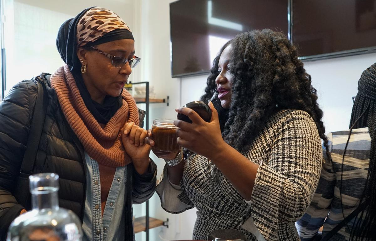 Monika Mathews, the owner of Queencare, right, shows Jamillah Goodrich one of the products sold in her new store in Columbia City. Photo by Susan Fried