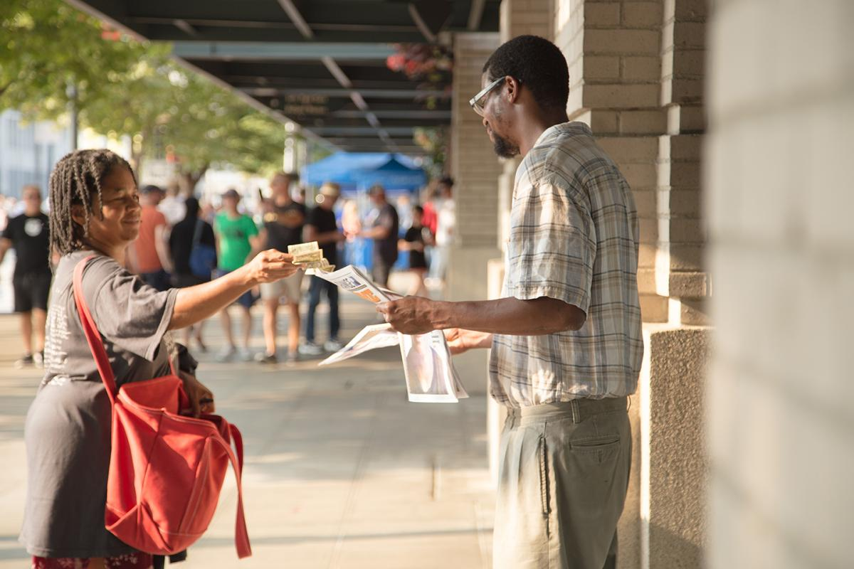 Vendor Michael Dotts sells a paper to a customer. Photo by Matthew S. Browning