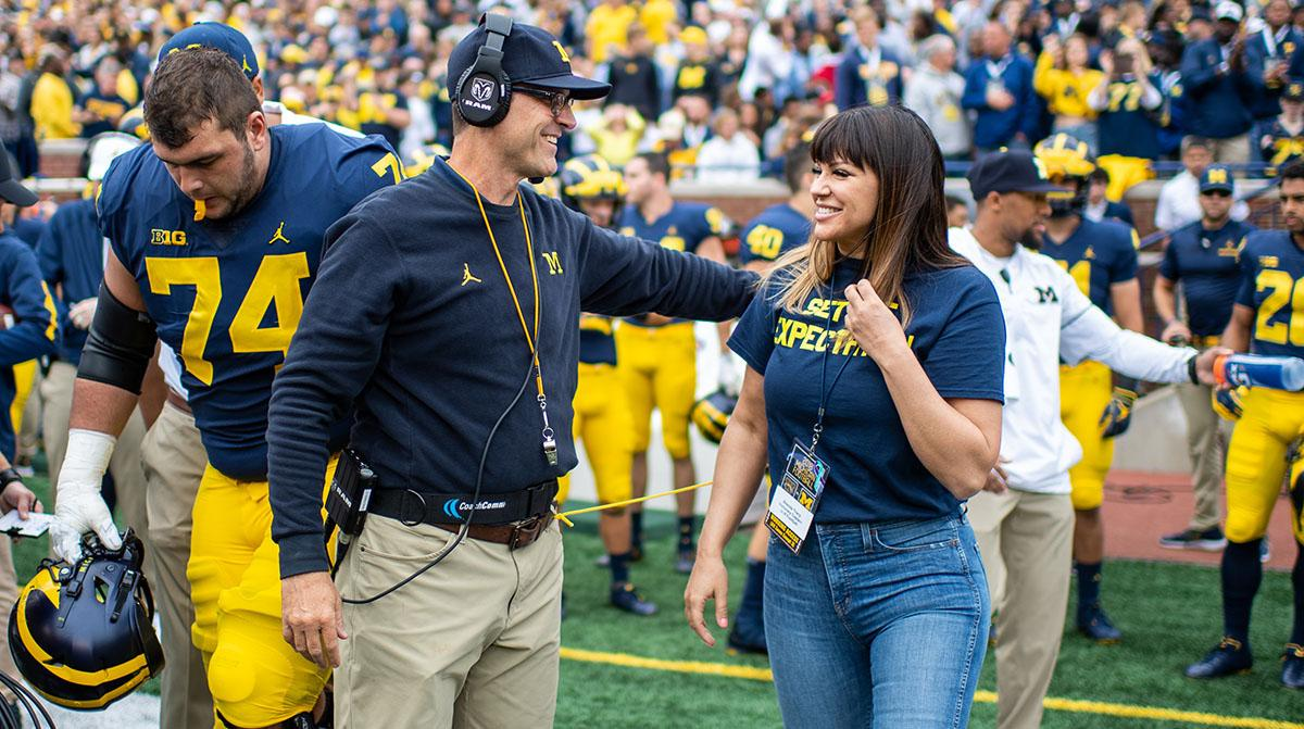 Brenda Tracy stands on the Michigan sideline with head football coach Jim Harbaugh during the Sept. 8 game against Western Michigan. Harbaugh made Tracy honorary captain after she spoke to the team about her #SetTheExpectation campaign to combat rape cult