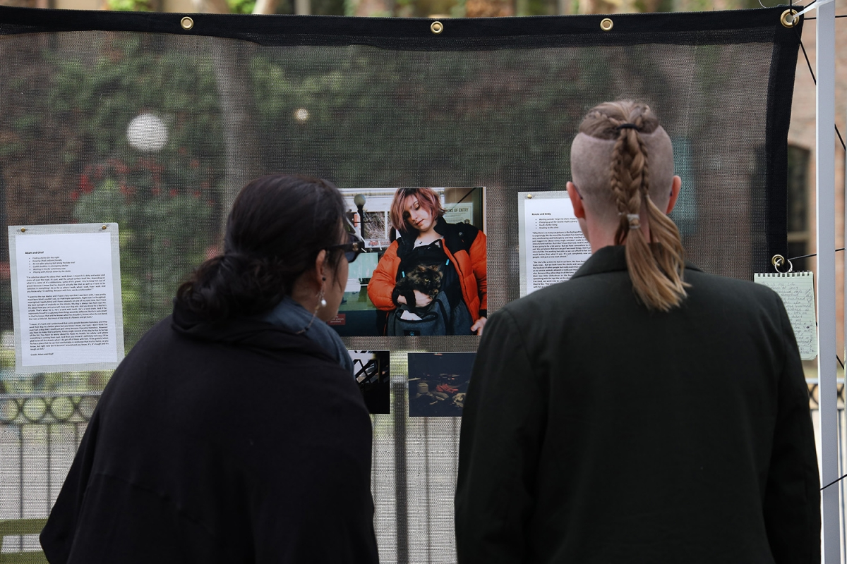 "Athena Prado Higgins, left, and Elsa Roberts look over the images and story provided by Kenzie and Andy in the ""Shifting the Focus"" exhibit in Occidental Park, Oct. 7. Photo by Jon Williams"