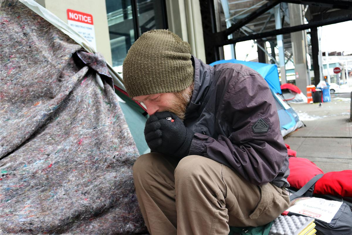Sean Struble tries to warm his hands while visiting the tent of a friend on Marion Street in downtown Seattle. Photo by Jon Williams