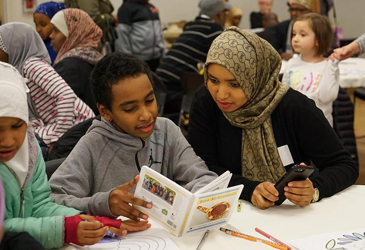"Families at New Holly Gathering Hall read ""Baro Af-Soomaali,"" a children's book about Somali culture created by local families. Photo by Susan Fried"