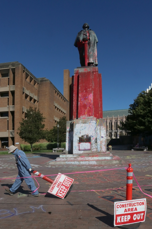 A worker from UW's Facilities department takes down a barrier that surrounded the statue, which was doused with red paint to symbolize blood. Photo by Jon Williams