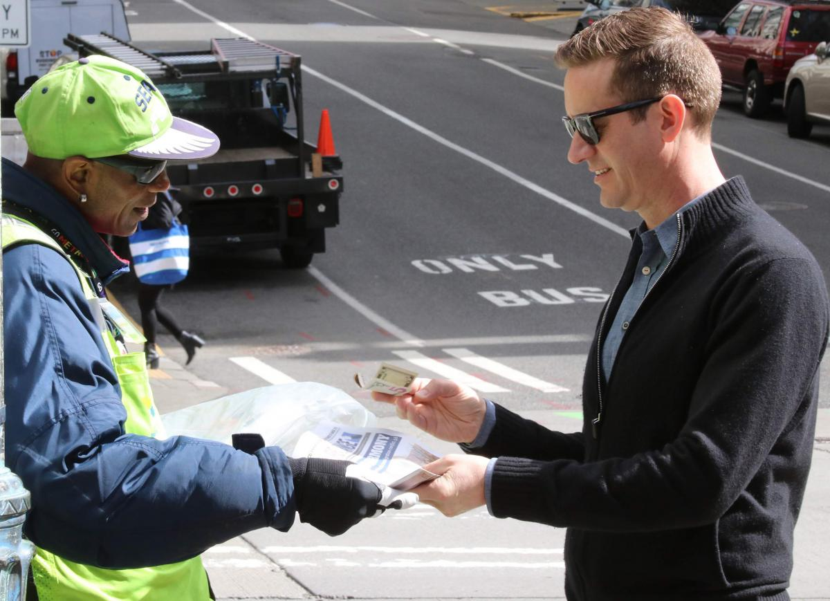 Vendor Zack Tutwiler sells a paper to a customer at Second and Cherry in Seattle. Photo by Jon Williams