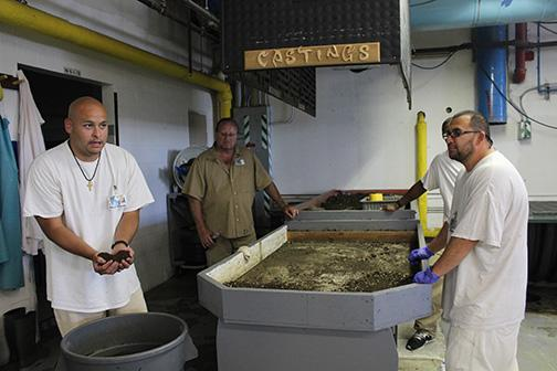​Juan Hernandez, left, explains the sorting process for collecting worm castings. Worm farmers sort out the cardboard and worms from the bins and filter the soil into a nutrient-rich fertilizer. Photo by Taylor McAvoy