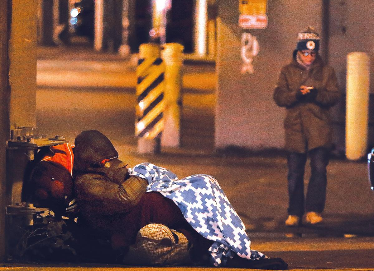 A volunteer walks the streets counting people who are homeless. One Night Count file photo.