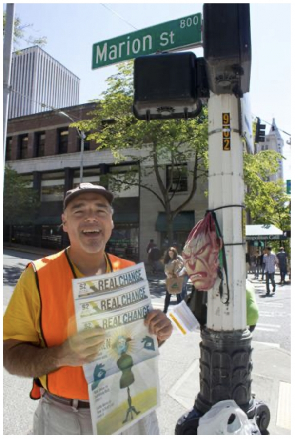 Jeffers holds up issues of Real Change with a special flair, while selling at one of several posts, including near the Real Change office on Marion Street in Pioneer Square.
