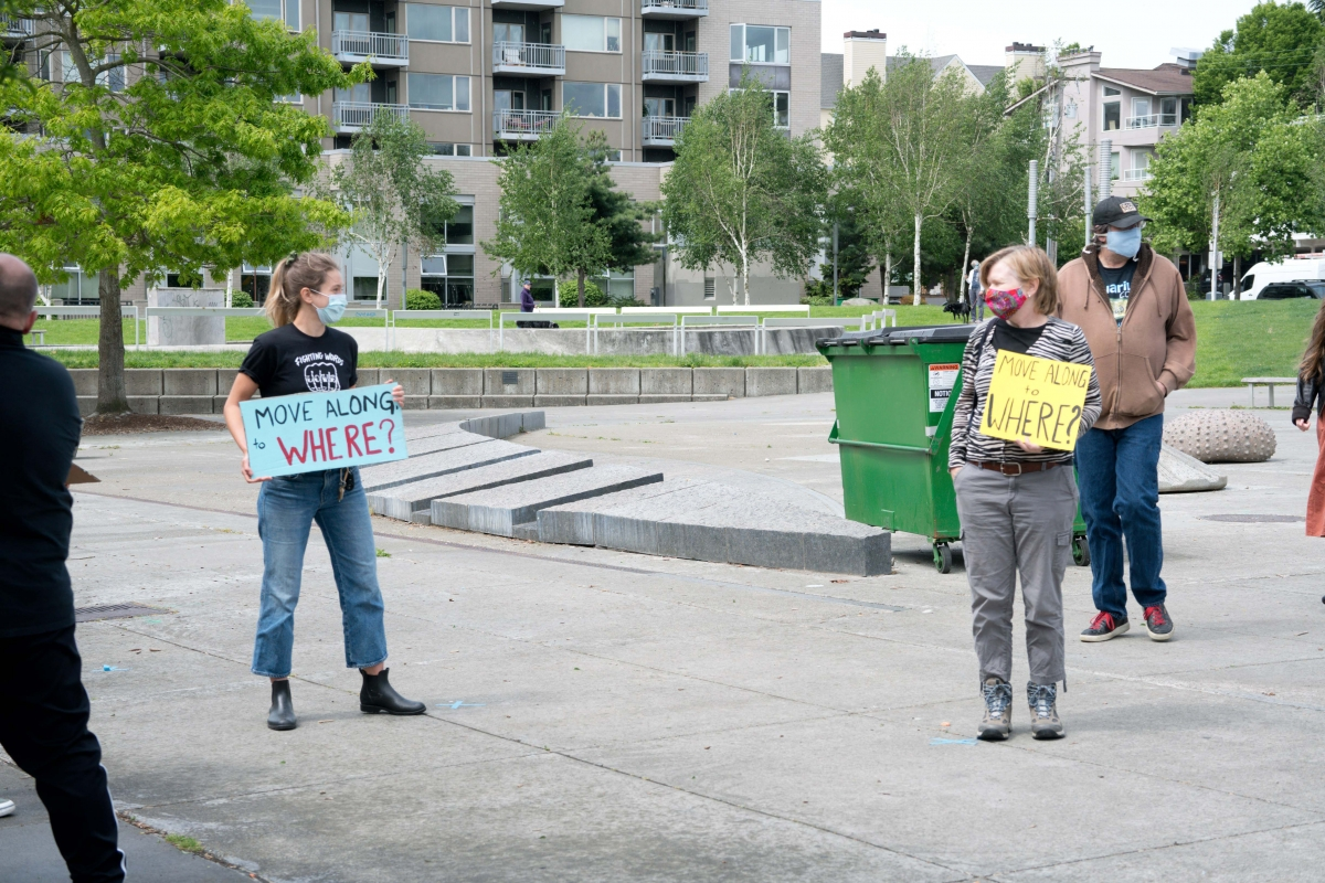 Future Real Change Executive Director Camilla Walter, left, makes her disapproval of sweeps known at a protest in the Ballard Commons, with volunteer Erin Rants and, far right, founder Timothy Harris, May 12, 2020.