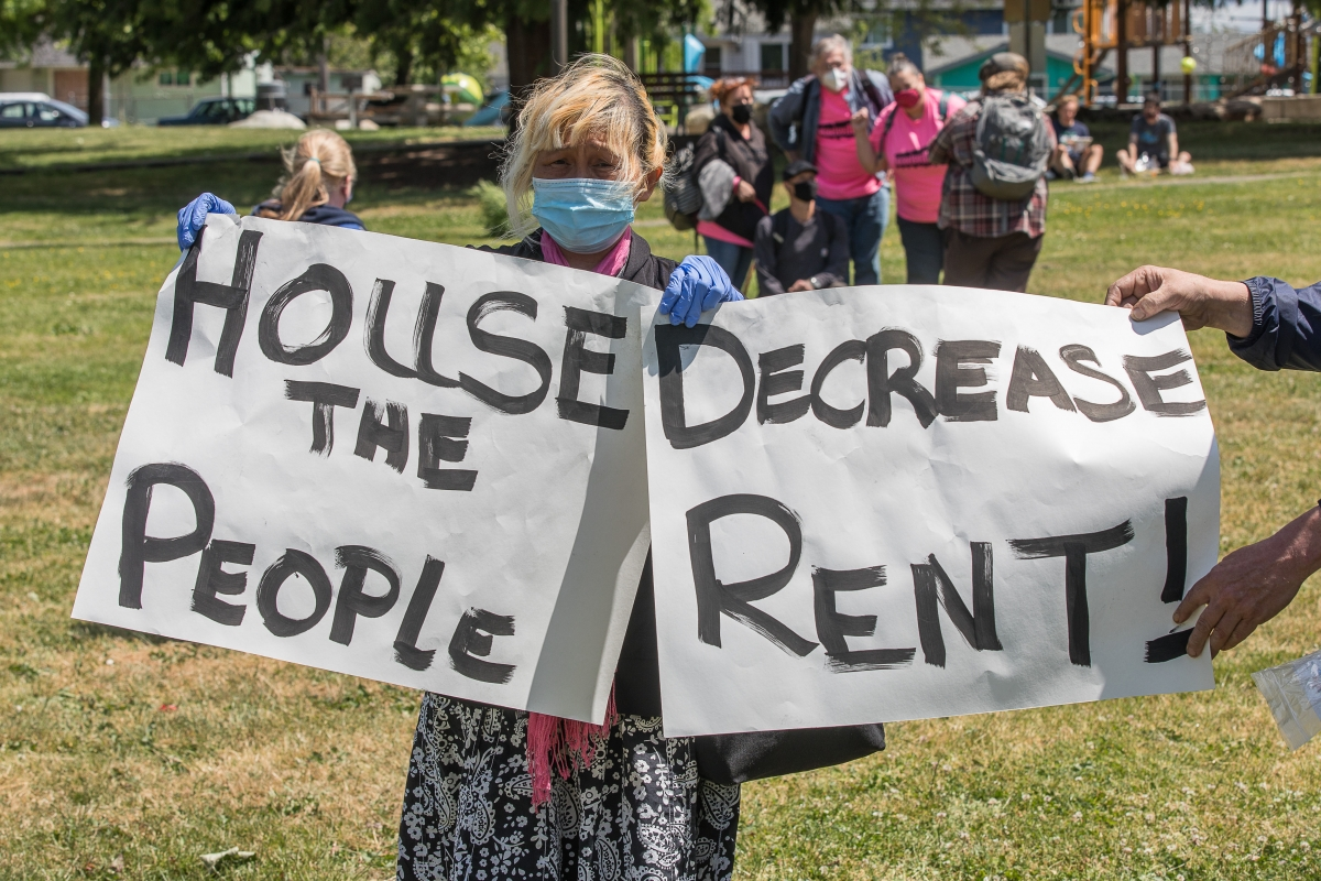 """In South Seattle's Othello Park, June 5, Heavenly Mountbatten holds petition signs at a rally that called for an extension of the pandemic's eviction moratorium and the """"cancellation"""" of rent owed. Mountbatten said she attended the rally because she belie"""