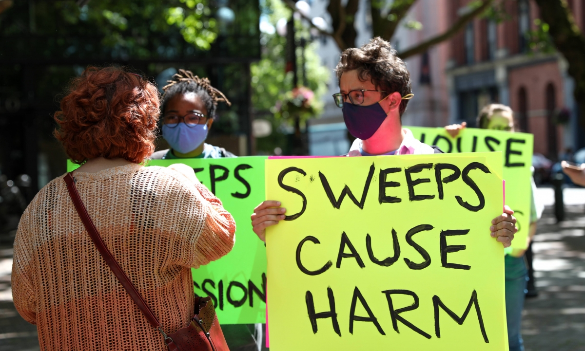 Advocate Tye Reed and Real Change Organizer Jacob Schear protest the mayor's continued policy of sweeps at the ribbon-cutting ceremony of Occidental Park in Pioneer Square, June 9. Photos by Samira George