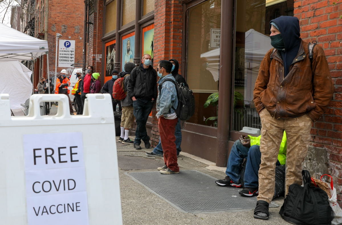 Nearby community members and Real Change vendors lined up for COVID-19 vaccines when a mobile vaccine unit showed up Friday, April 2, outside Real Change offices in Pioneer Square. Photo by Samira George