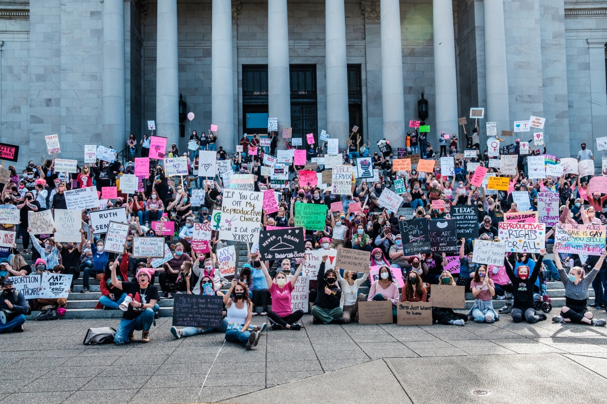People fill the streets surrounding the Capitol campus, holding signs decrying efforts to restrict abortion access.