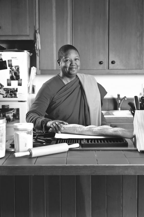 The Venerable Pannavati, the world's only black Buddhist nun, is in a kitchen. She has one hand placed on a loaf of bread. In the foreground is jar and rolling pin, and a fridge in the background.