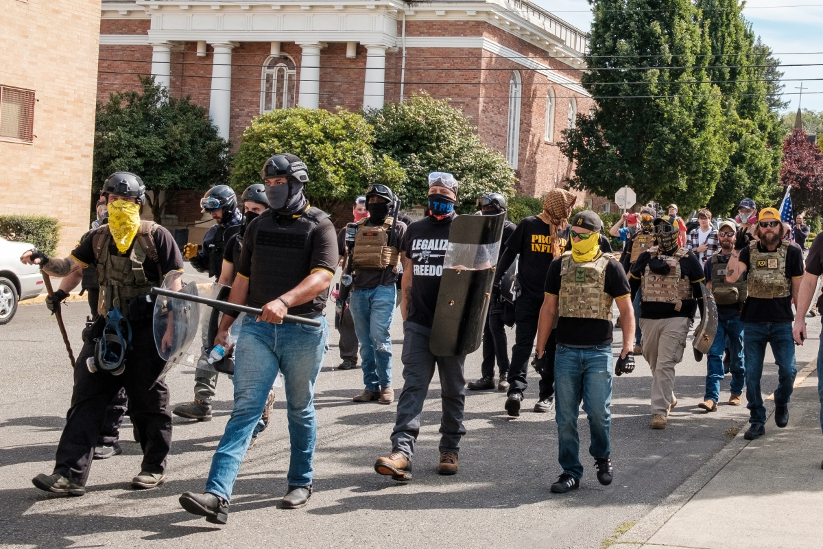 """Members of the Proud Boys took to the streets in Olympia, Sept. 4. In the front row of the group, in blue jeans and holding a baton, appears to be Tusitala """"Tiny"""" Toese, a leader of the Proud Boys, who was shot in the foot later that afternoon. Photos by"""