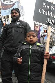 """A young marcher carries a """"No New Children's Jail"""" sign at the 2015 MLK March in Seattle. Real Change file, 2015"""