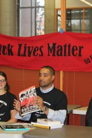 History teacher Jesse Hagopian lifts up culturally relevant curriculum materials at a press conference to announce new initiatives to support Black students at Seattle Public Schools.