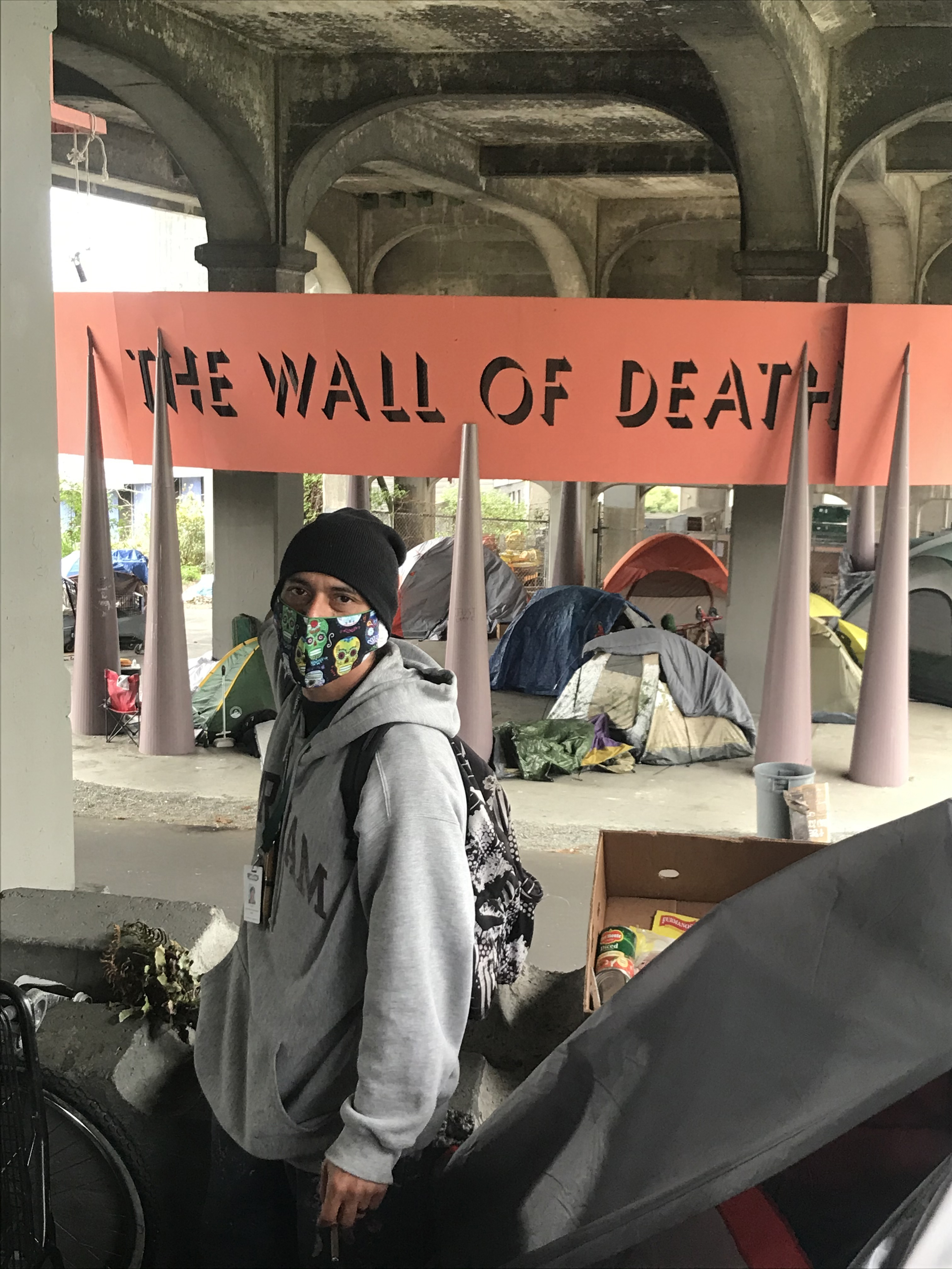 """As the REACH neighborhood care coordinator, David Delgado works directly with unhoused people in the Seattle area, such as the community camping under the University Bridge near the permanent art installation """"The Wall of Death,"""" to try to connect them wi"""