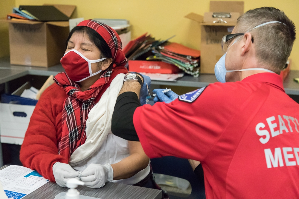 """Grocery worker Melva receives her first dose from a member of the Seattle Fire Department. She had contracted COVID-19 in December. """"I was worried that I would have it again and die,"""" she said, """"I'm so excited."""""""