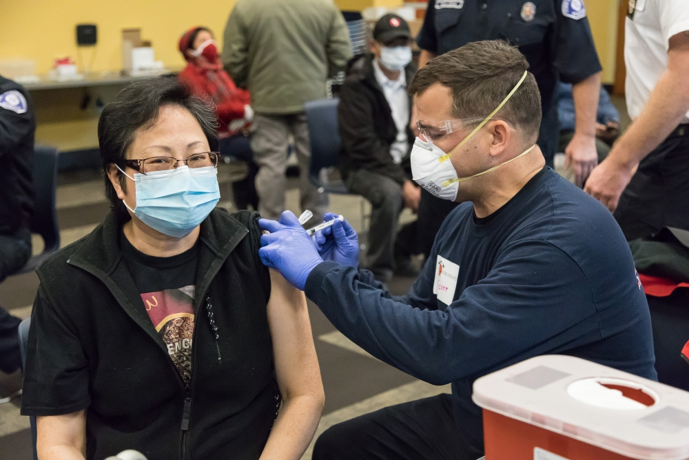 """Grace Shen receives a COVID-19 vaccination from firefighter Scott at the UFCW 21 event on January 31, 2021. """"Send me a photo,"""" Shen said, """"this is special."""""""