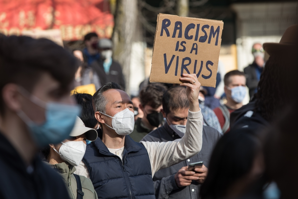 "A rally participant holds a ""Racism is a virus"" sign."
