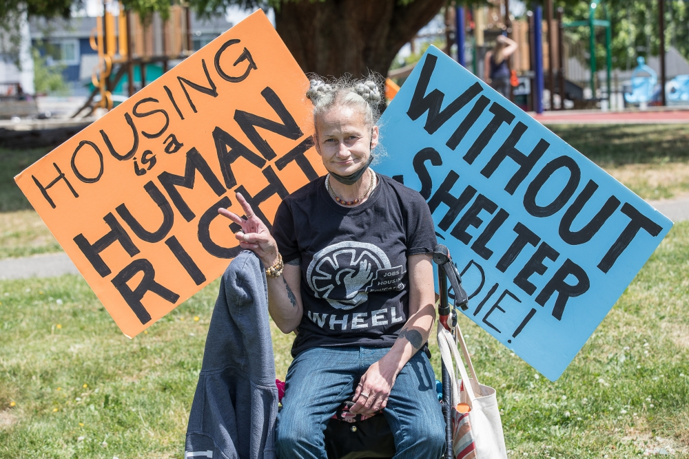 """Heather Kilgore sits beside signs reading """"Housing is a human right"""" and """"Without shelter, people die!"""" Kilgore is currently unhoused and attended the rally in support of Seattle Women's Housing Equality and Enhancement League."""