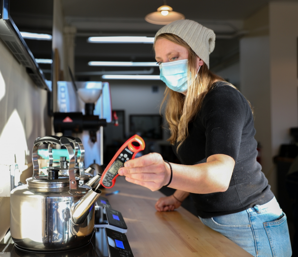 Susan Wilcox measures the temperature of water for the daily coffee-cupping process, while wearing a quarantine face mask, at Sucafina Speciality in Seattle's Fremont neighborhood. Sucafina also has a location in New York City.