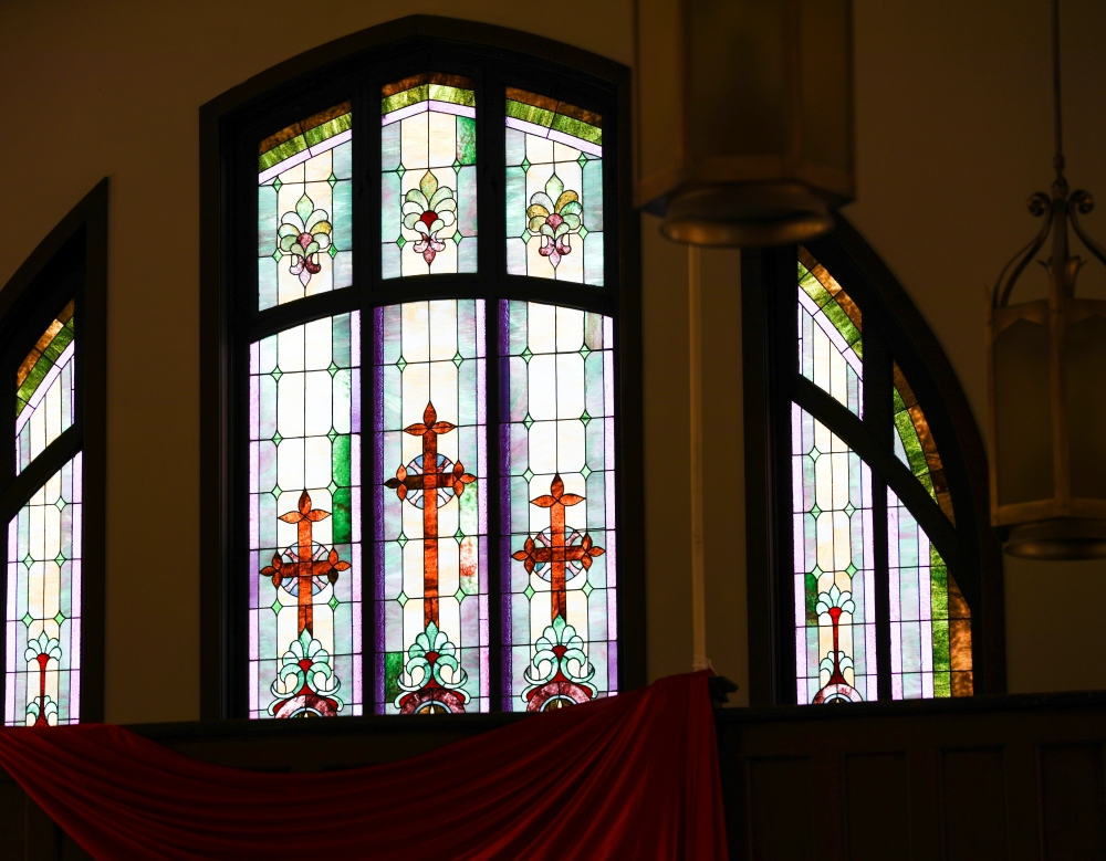 Stained glass windows on various walls of the church bring multicolored light onto the altar and pews.