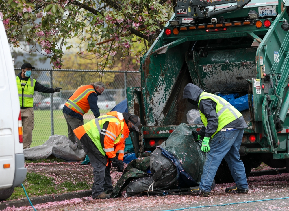 City employees are tasked with forcing out unhoused people by throwing their possessions away in garbage trucks.