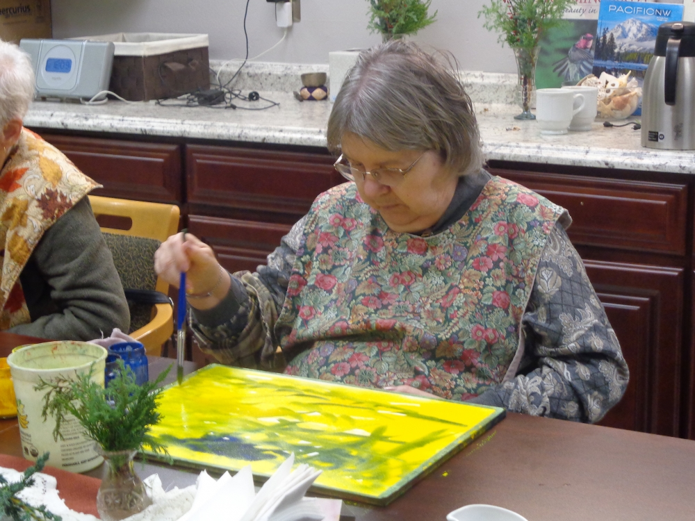 Julia Blackburn works on a painting while at Elderwise during their adult day program.