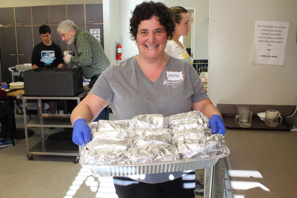 Laura Silverstein carries a large allotment of finished burritos. Photo by Dave Parish