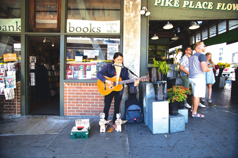 Fernando Gramal plays his guitar and panflute in front of Left Bank Books. Gramal has been playing in Seattle more than 10 years. Photo by Matthew S. Browning