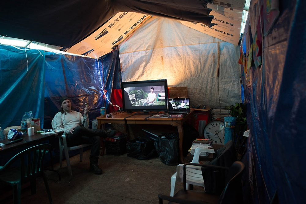 "Residents of Camp Second Chance watch ""Neighbors 2"" in a tent structure insulated with warm blankets and plastic tarping. The camp receives electricity from a generator. Photo by Sarah Sha"