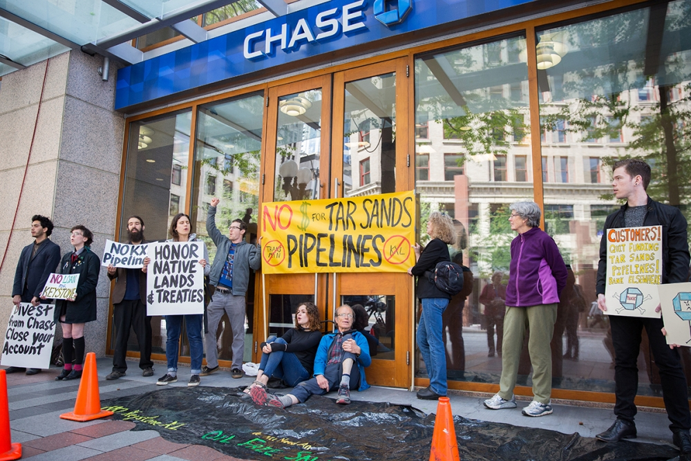 Jim McMahan and Andrea lock themselves to the Chase doors on Fourth Avenue across from Westlake Park in protest of Chase's funding of the Keystone XL Pipeline. Photo by Alex Garland