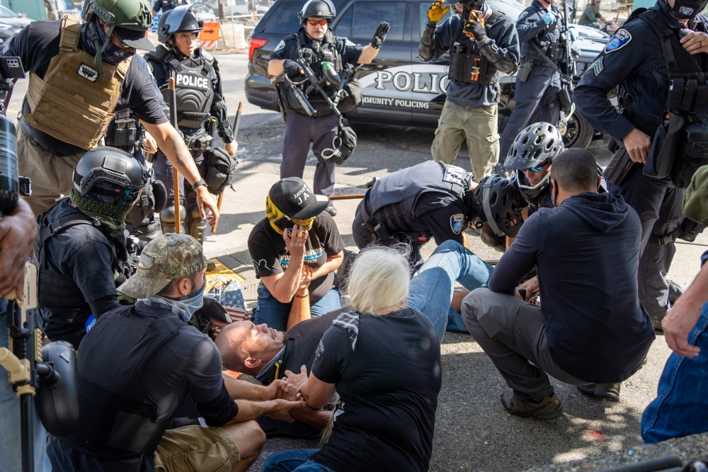 Onlookers gave Tusitala Toese comfort as Olympia police provide emergency aid, after the Proud Boys leader was shot in the foot, Sept. 4. Toese was brought to an area hospital, and his wounds were not life-threatening. Reports are mixed on who shot Toese.