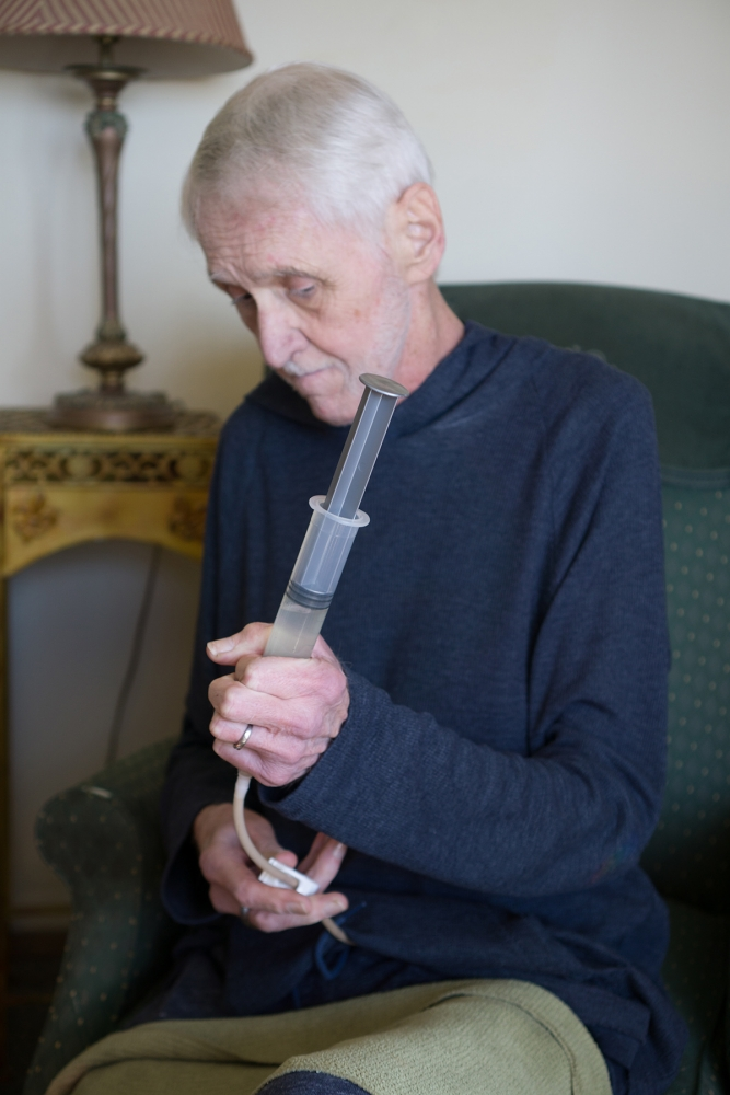 Robert Fuller injects a morphine solution through his gastric tube. Photo by Wes Sauer