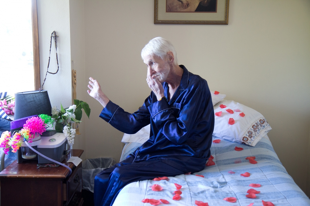 Robert Baxter-Fuller sits on his bed in blue pajamas. The clock, above, ticked down the minutes until 3 p.m. when Fuller would ingest his life-ending medications. Photo by Wes Sauer