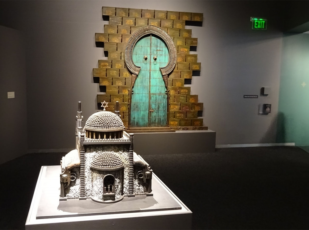 """Synagogue (III),"" 2010, guns, gun parts, bullets, steel, shot, polycarbonate, Israeli Army issue Tefilin bag; ""Vandalized Mosque Door,"" 2016, ammo boxes, guns, gun parts, bullets, shell casings, steel, wood, paint, cluster bomb parts. Photo by Lisa Edge"