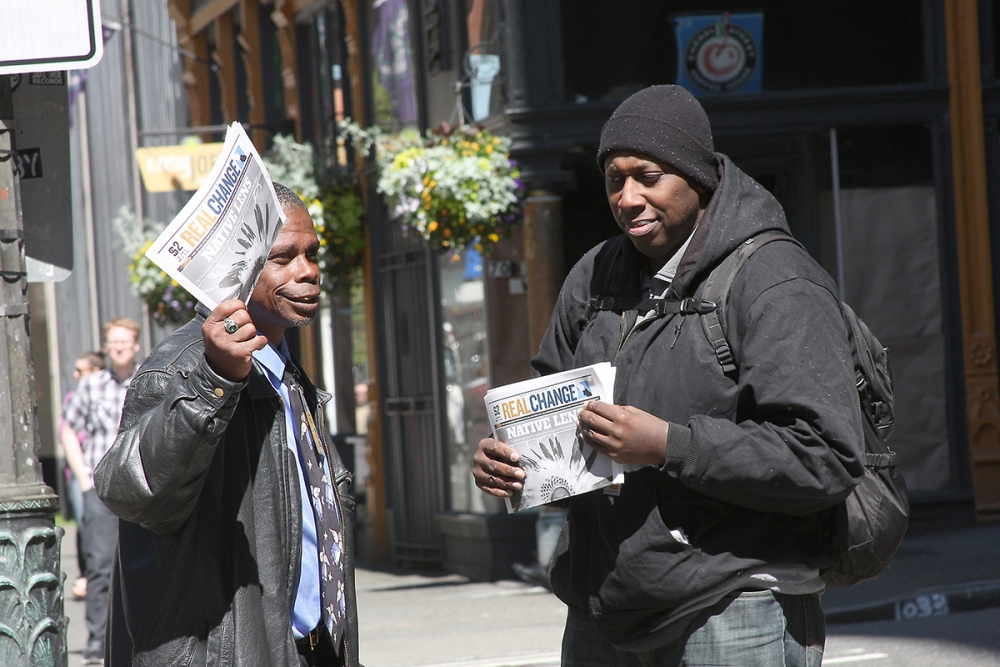 Donald Morehead (left) trains a new vendor. Photo by Jon Williams